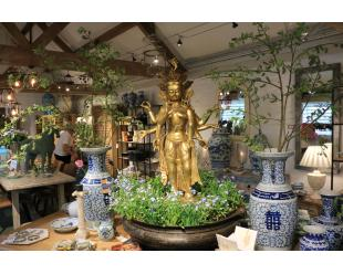 Indigo Antiques showroom showing a bronze Tibetan goddess amongst a selection of blue and white china